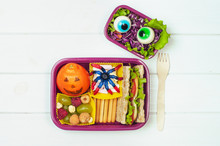 Open Halloween Lunch Box With Sandwich, Mandarin, Berries And Vegetable Salad On White Background With Blank Space For Text