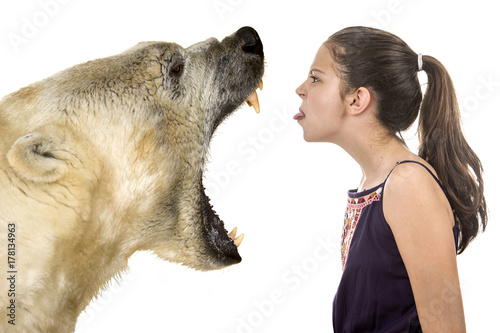 Young fearless girl with a polar bear on a white background Fototapet