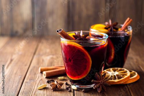 Plakat Dwa szkła boże narodzenia rozmyślali wino z pomarańczami i pikantność na drewnianym tle.