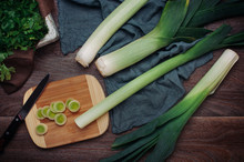 Three Stalks Of Leek On The Rustic Wooden Background