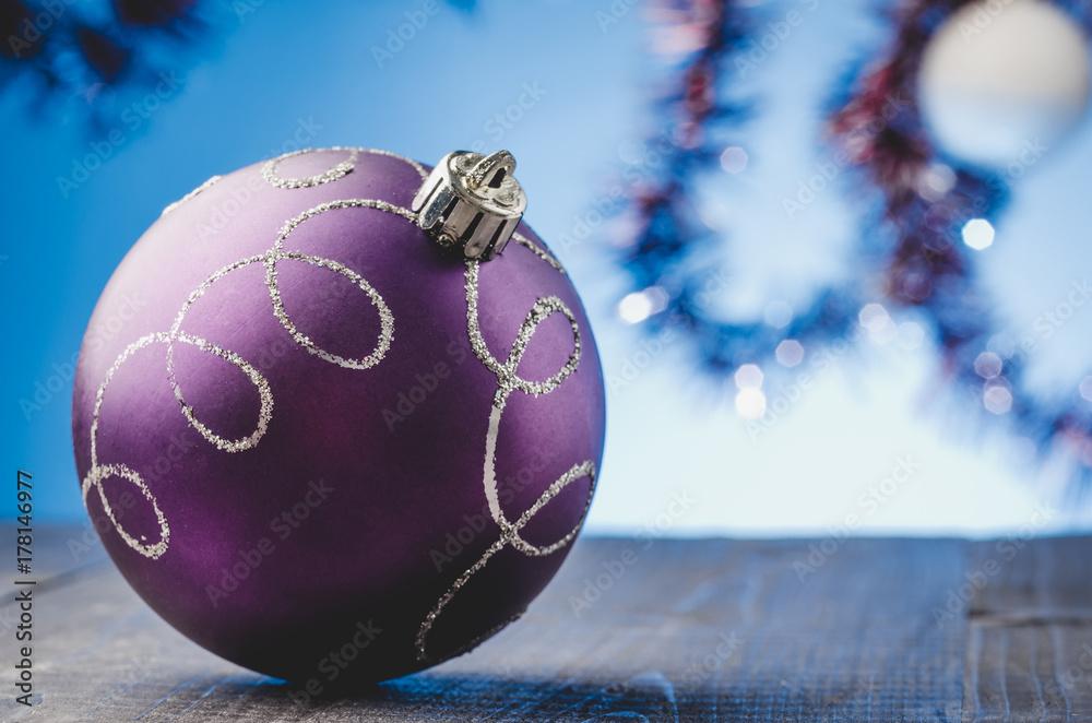 fotografija violet christmas ball on a blue light background violet christmas ball on a blue light background na europosterji si