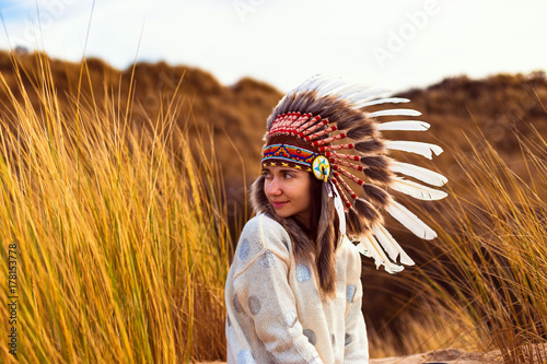 Photo  Beautiful young woman in black dotted white chief style Native American headdres