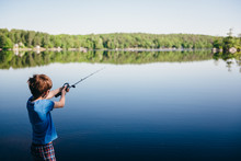 Boy Casts His Fishing Pole Into A Lake