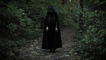 Black Witch Is Wearing Black Coat With Hood Sliding On A Face, Is Standing Still On A Path In A Dens Dark Forest
