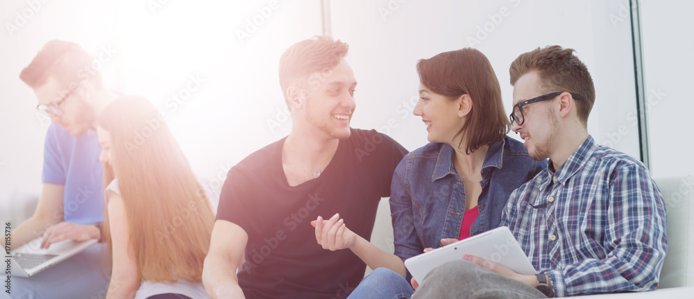 Fototapeta Group of young people in casual clothes chatting and having fun