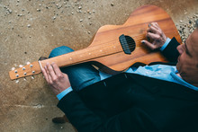 Male Musician Playing A Slide Guitar By A Loading Dock