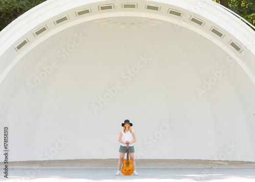 Fototapeta Kobiety pozycja bawić się na gitarze akustycznej outside