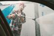 Man washes his car at the car wash