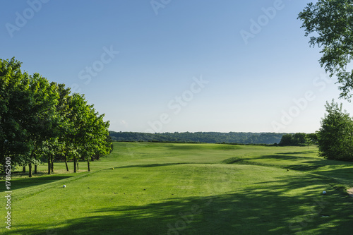 Slika na platnu General view of a green golf course on a bright sunny day