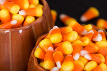 Pumpkin Cups Filled With Halloween Candy Corn. Closeup With Dark Background.