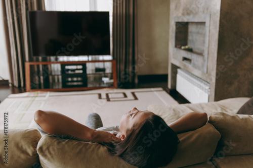 Zdjęcie XXL Młoda kobieta w domu, leżąc na kanapie, relaks w jej salonie i oglądania telewizji. Ścieśniać. Widok z tyłu. Z miejscem na tekst.