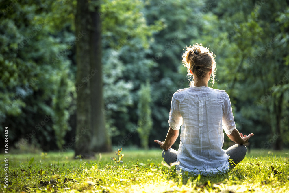 Fototapeta Woman meditating and practicing yoga in forrest