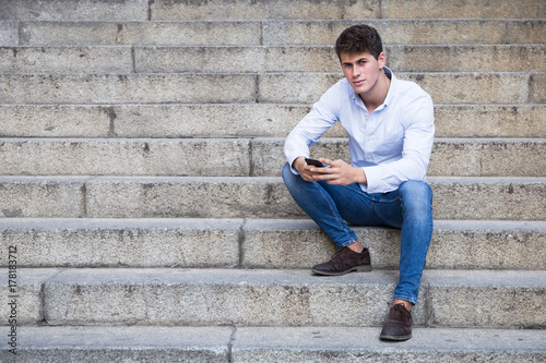 Handsome young man in shirt and jeans sitting on stairs and using his smartphone looking at camera