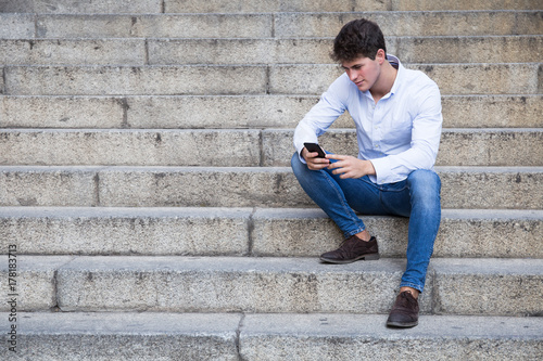 Handsome young man in shirt and jeans sitting on stairs and using his smartphone.
