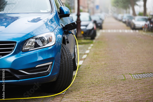 Photo The car being charged on a street of a city
