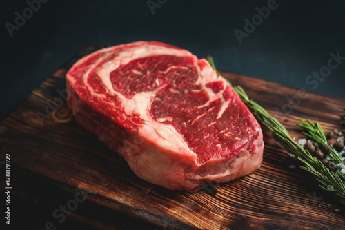 Fotografiet raw rib eye steak on a wooden Board on black background - rustic stule