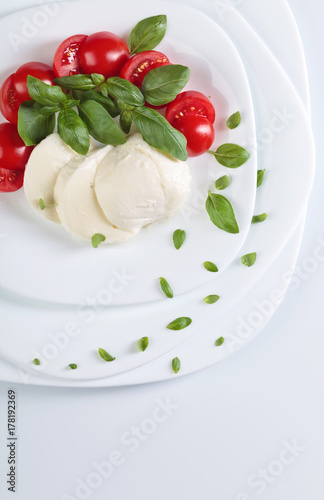Plakat Mozzarella z pomidorami i zieloną bazylią.