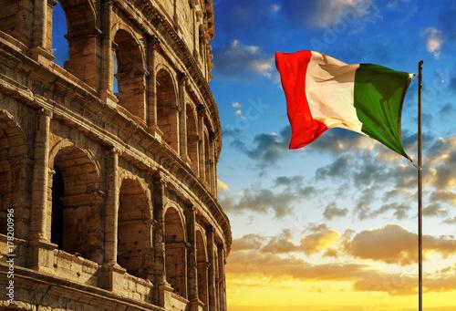 Fényképezés  Italian flag with Flavian Amphitheatre or Colosseum at sunset