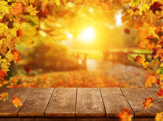 Autumn background with falling leaves and empty wooden table
