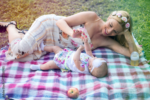 Zdjęcie XXL Matka i dziecko leżącej na koc piknikowy i zabawę razem na zewnątrz.