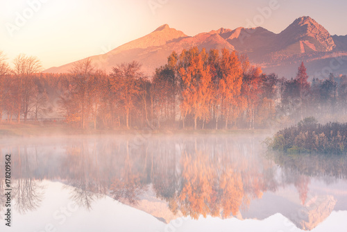 Foto auf Leinwand Lachs Sunrise light hits high mountains peaks in Tatra mountains