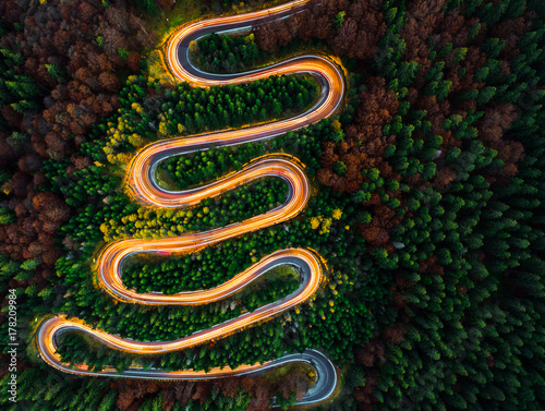 Fotografia, Obraz  Aerial view of light trails on a winding road through the forest in fall