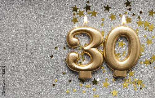 Fotografia  Number 30 gold celebration candle on star and glitter background
