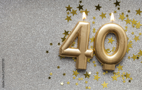 Fotografia  Number 40 gold celebration candle on star and glitter background