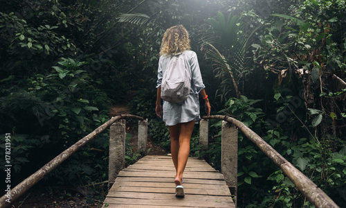 Poster Lieu connus d Asie View from the back photo of young caucasian female with curly hair walking the old wooden bridge in the jungles. Backpacker female is exploring tropical forest during summer vacation.