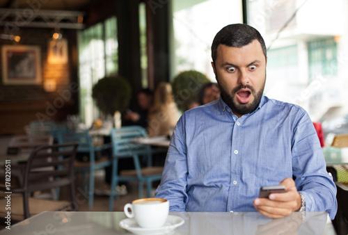 Portrait of shocked man looking at phone Fototapete