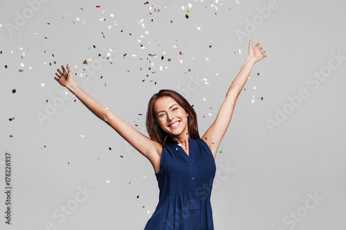 Fotografija  Beautiful happy woman at celebration party with confetti falling everywhere on her