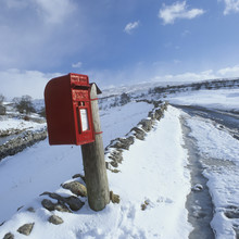 Traditional Red Postbox In A Rural Setting In The Snow