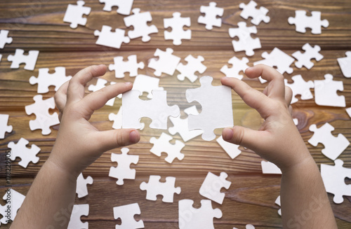 Fototapety, obrazy: The child's hands collect puzzles, docking two parts. Concept of education, business