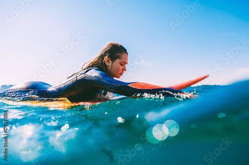 Plakat Surfer dziewczyna na deskę surfingową. Młoda kobieta w oceanie podczas surfingu.