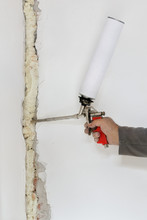 Worker Fixing Hole In Wall Usi...