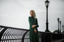 Lady In Green Dress Poses On The Embankment In A Foggy Day