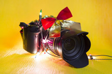 Camera As A Gift For The New Year. A New Camera Is The Best Gift For A Photographer For The New Year. A Camera In A Festive Garland And A Bow On A Yellow Bright Background