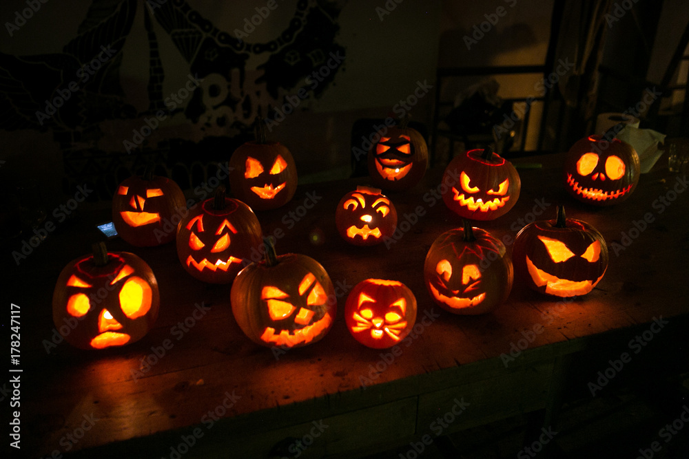 Soft focus shot of halloween pumpkins lined up on table in thematic cafe or big family house. Candles lit up inside for spooky and evil effect, atmosphere of autumn holiday