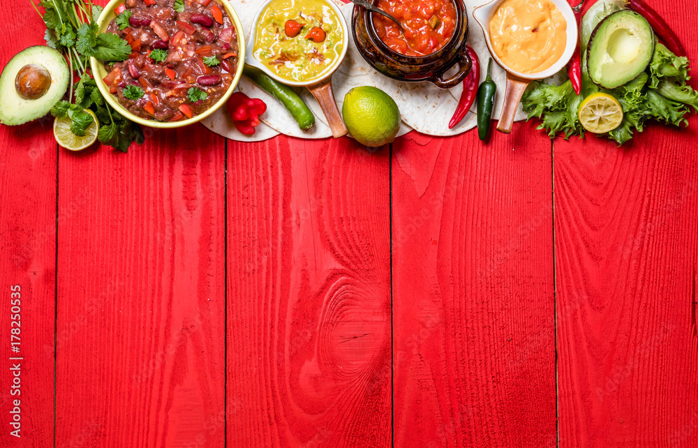 Fototapety, obrazy: Vegetarian Mexican food concept: refried black and red beans. guacamole, salsa, chili, tortilla chips and fresh ingredients over vintage red rustic wooden background. Top view, flat lay