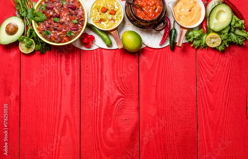 Vegetarian Mexican food concept: refried black and red beans. guacamole, salsa, chili, tortilla chips and fresh ingredients over vintage red rustic wooden background. Top view, flat lay