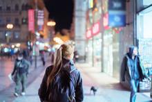 Back View Of Girl Walking On City Street At Night, Prague