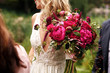 canvas print picture - Pretty bride holds rich dark pink bouquet of peonies in her arm