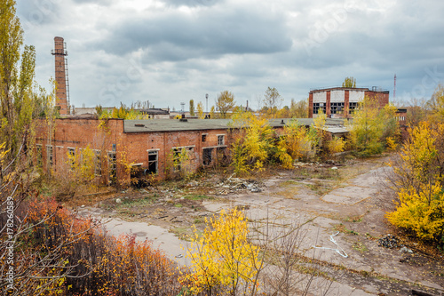 Staande foto Industrial geb. Old obsolete ruined overgrown concrete industrial buildings in autumn. Abandoned factory