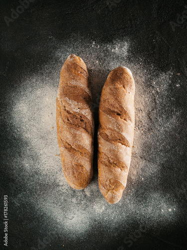 Plakat Dwa cały domowej roboty gryczany bochenek chleb z gryczaną mąką na czarnym textured tle. Widok z góry lub płasko ułożony. Niski klucz