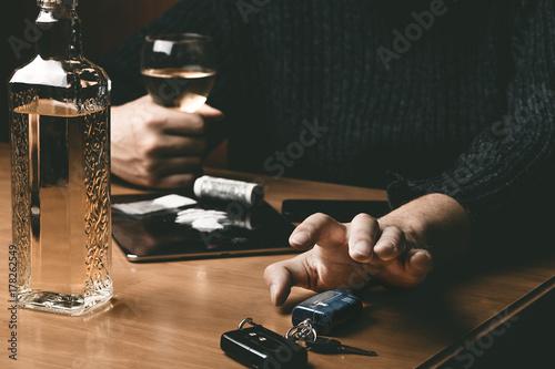 Valokuva  Man takes car keys after using cocaine drug and drinking whiskey