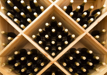 Stacked Bottles Of Grape Wine In A Wine Cellar