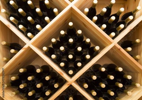stacked bottles of grape wine in a wine cellar Fototapet