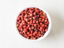 Pile With Dried Pink Pepper Berries On White Wooden Table. Close Up View Of Pink Peppercorn. Top View Or Flat-lay.