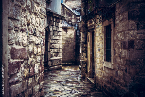 Dark vintage medieval narrow winding street with ancient stone building facade with medieval architecture in old european city Kotor in Montenegro
