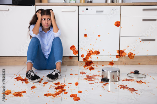 Fotografia  Woman Sitting On Kitchen Floor With Spilled Food